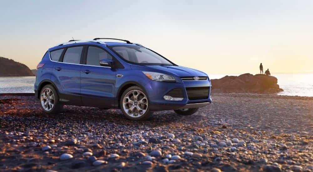 A blue 2013 used Ford Escape is parked on a rocky beach.