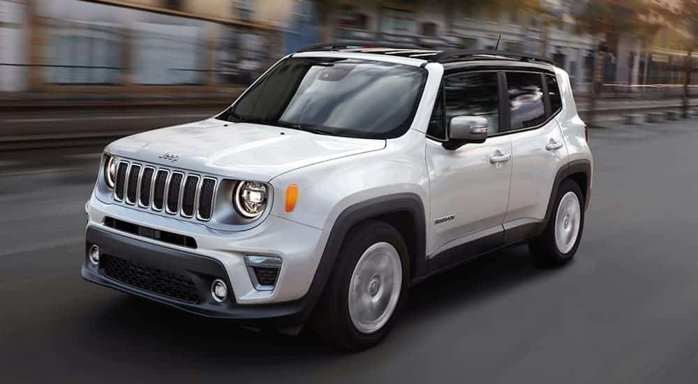 A white 2020 Jeep Renegade is driving on a city street.