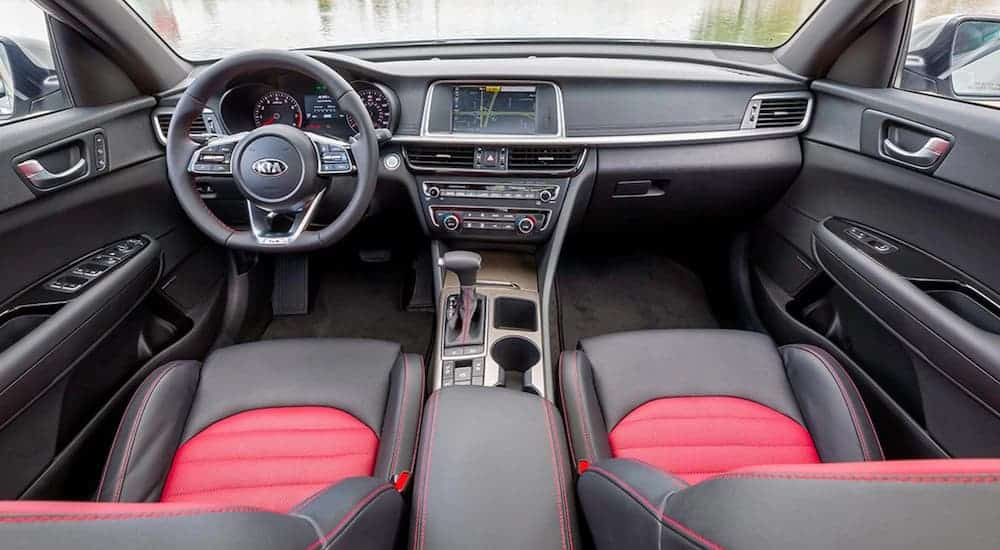 The black and red interior of a 2020 Kia Optima is shown.