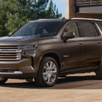 A brown 2021 Chevy Tahoe is parked in front of a garage.