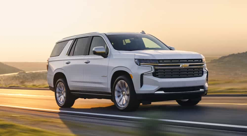 A white 2021 Chevy Tahoe is driving out of a corner past hills at sunset.