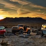 In a comparison of the 2021 Ford Bronco vs 2021 Ford Bronco Sport, three models are parked in front of a sunset behind mountains.