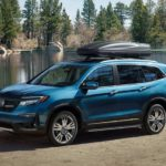 A blue 2021 Honda Pilot is parked in front of a pond with a luggage carrier on top.
