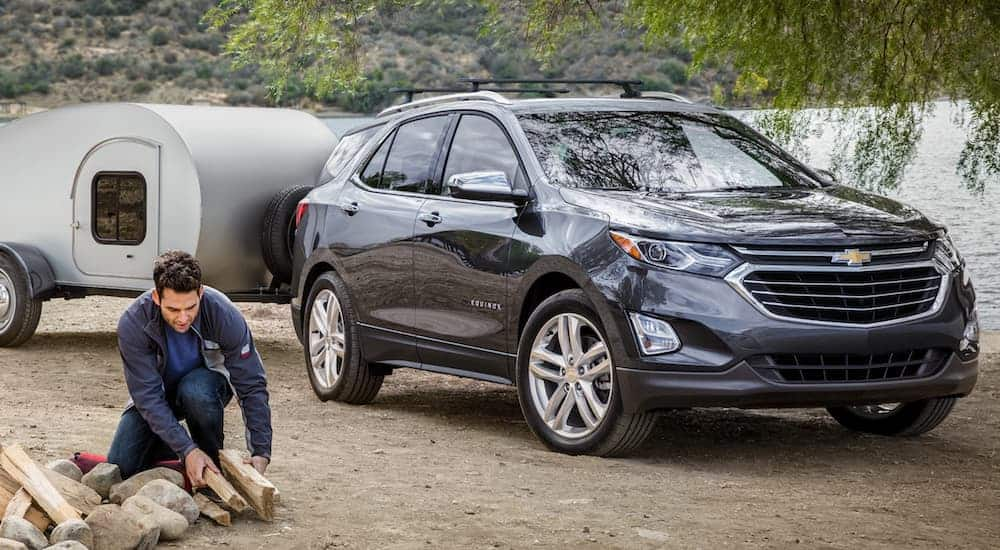 A dark grey 2020 Chevy Equinox is at a campsite with a tear drop camper as a man lights a fire.