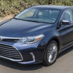 A blue 2017 Toyota Avalon from your local used car dealership is driving on a desert highway.