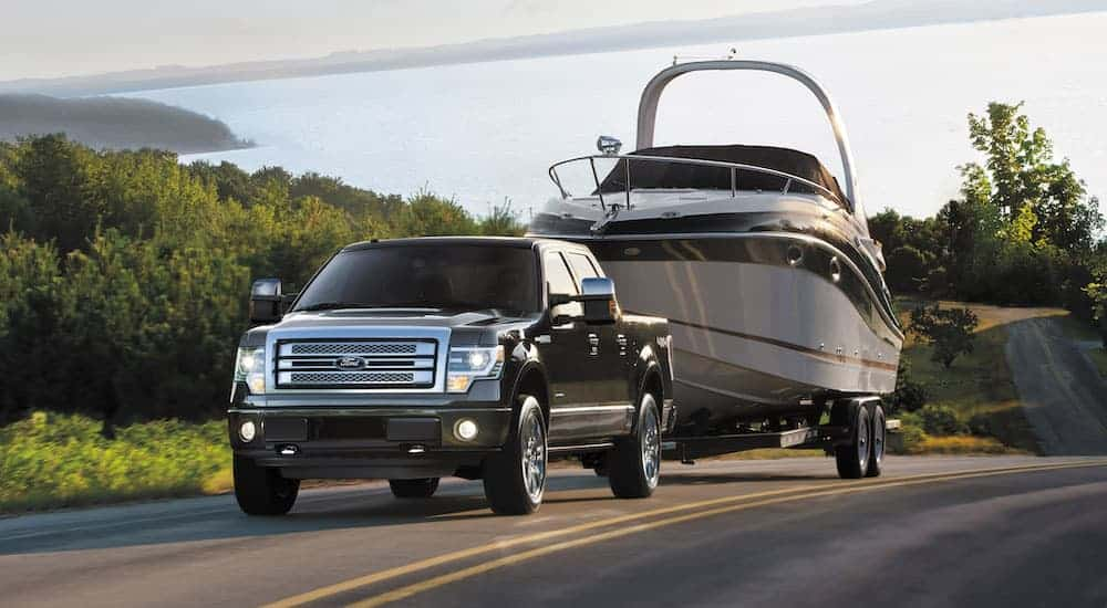 A black 2014 Used Ford F-150 is towing a large boat uphill with a lake in the distance.