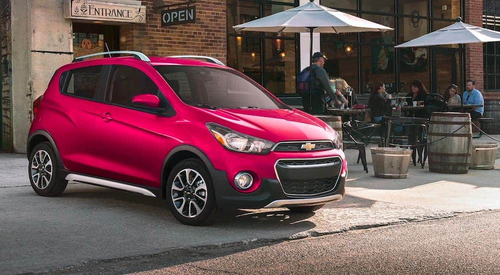 A red 2021 Chevy Spark is parked outside a cafe.