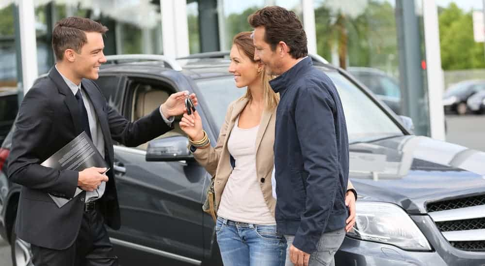 A salesman is talking to a couple next to a grey SUV at a used car dealership.