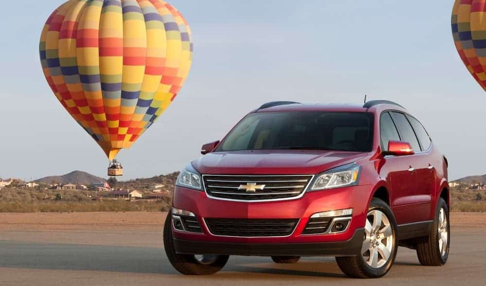 A red 2016 Used Chevy Traverse LTZ is parked in front of a multicolored hot air balloon.