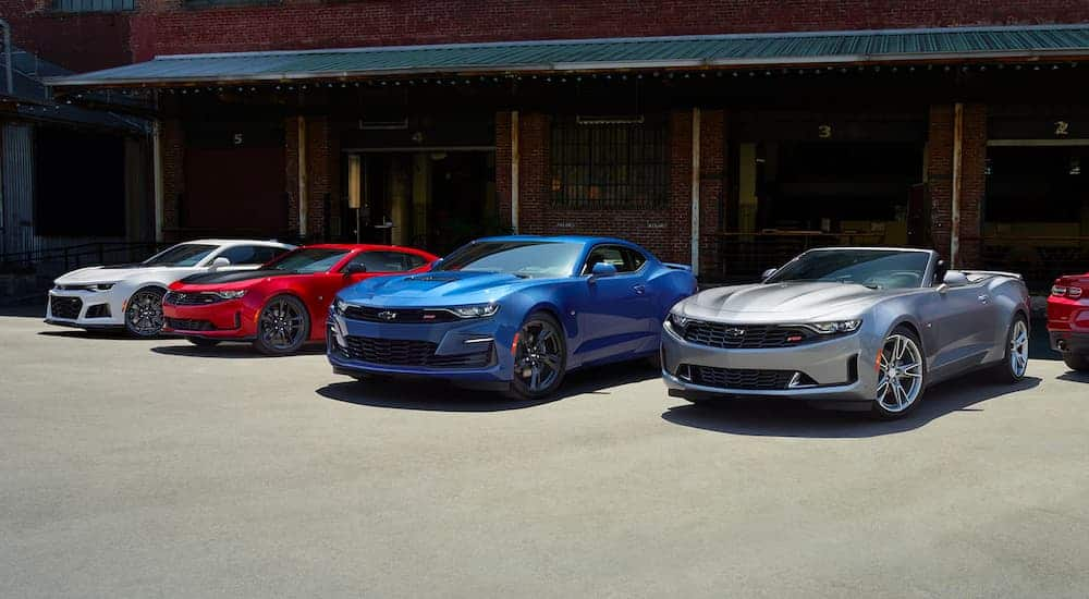 Four 2021 Chevrolet Camaros a silver, a blue, a red, and a white are all parked in front of a warehouse.