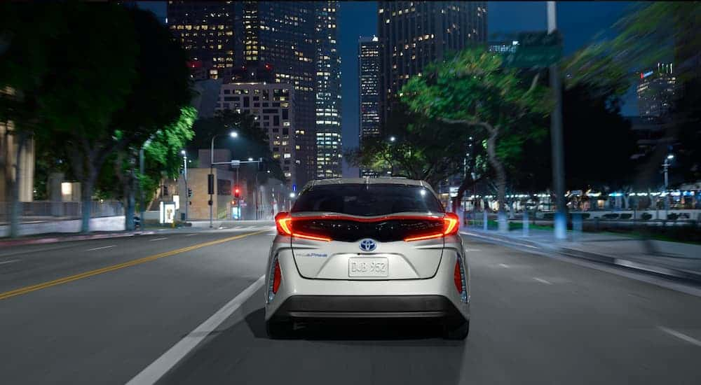 A silver 2021 Toyota Prius Prime LE is shown from the rear driving down a city street.