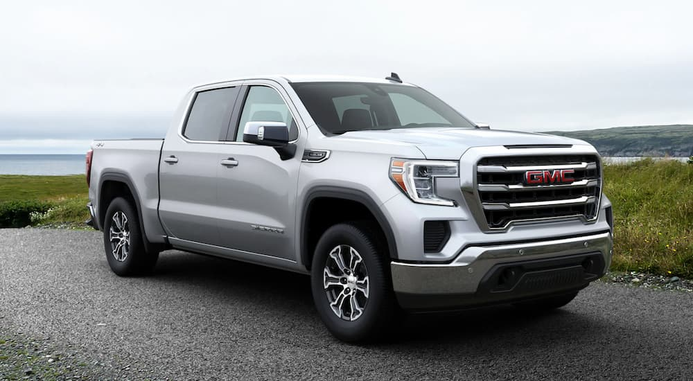 A silver 2020 GMC Sierra 1500 is parked next to a large lake.