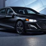 A black 2021 Chevy Malibu is parked in front of a modern building with the headlights on.