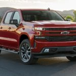 A red 2021 Chevy Silverado 1500 is parked in front of a farm after winning the 2021 Chevy Silverado 1500 Diesel vs 2021 Ram 1500 Diesel comparison.