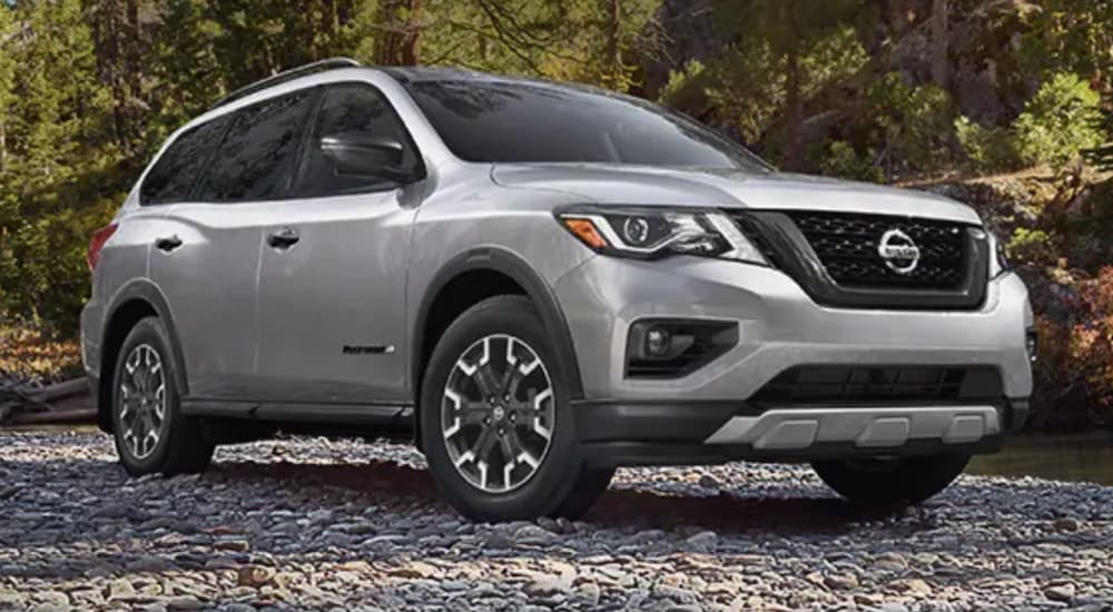A silver 2020 Nissan Pathfinder is parked on a rocky river shore.