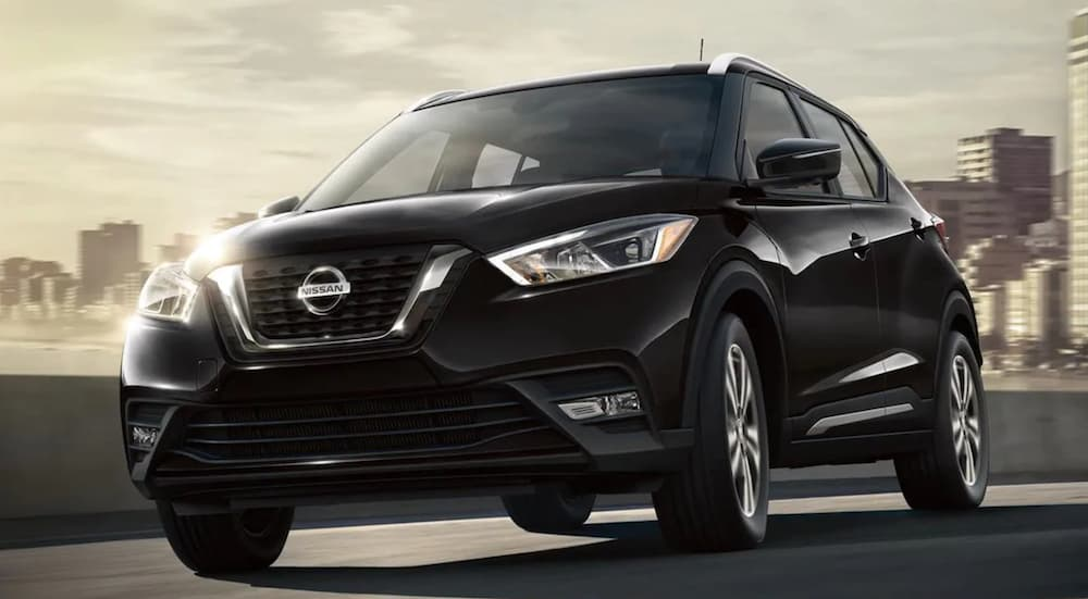 A black 2020 Nissan Kicks is driving away from a city.