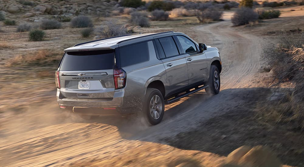A grey 2021 Chevy Suburban is driving on a dirt road past shrubs.