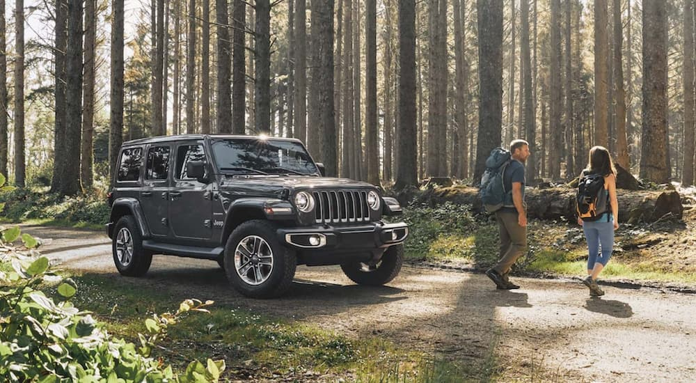 A couple is walking away from a grey 2020 Jeep Wrangler Unlimited in the woods with back packs.