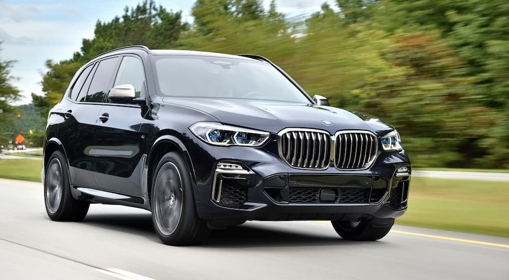 A black 2018 Used BMW X5 is driving on a highway past trees.