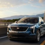 A blue 2019 used Cadillac XT4 is driving over a bridge.