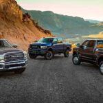 A brown, a blue, and a black 2019 used Ram 2500 are parked on a mountain road in the desert.