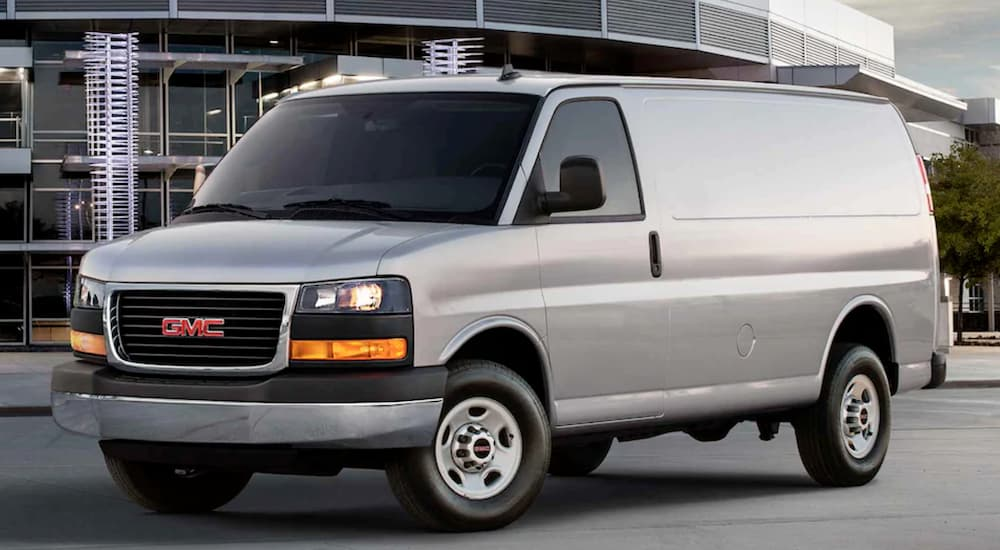 A grey 2021 GMC Work Van Savana is shown from the side in front of a modern building.