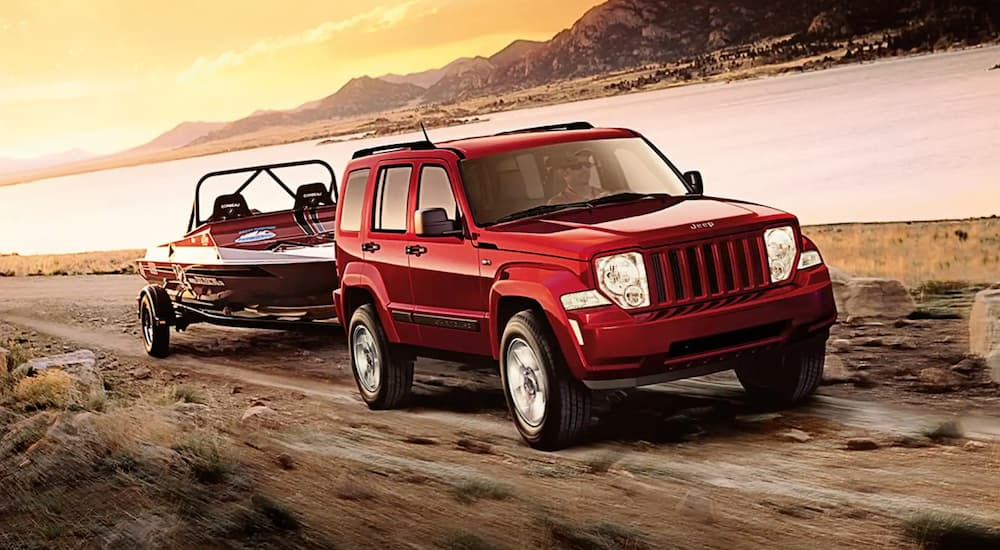 A red 2011 Jeep Liberty is towing a boat past a lake at sunset.