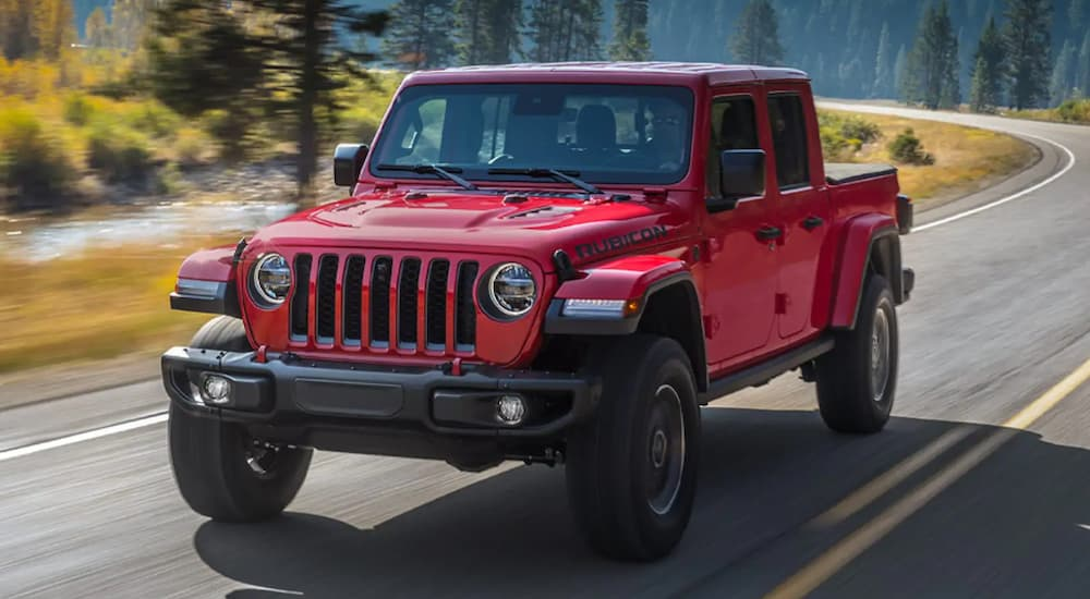 A red 2021 Jeep Gladiator is driving on a road past a corner and trees.