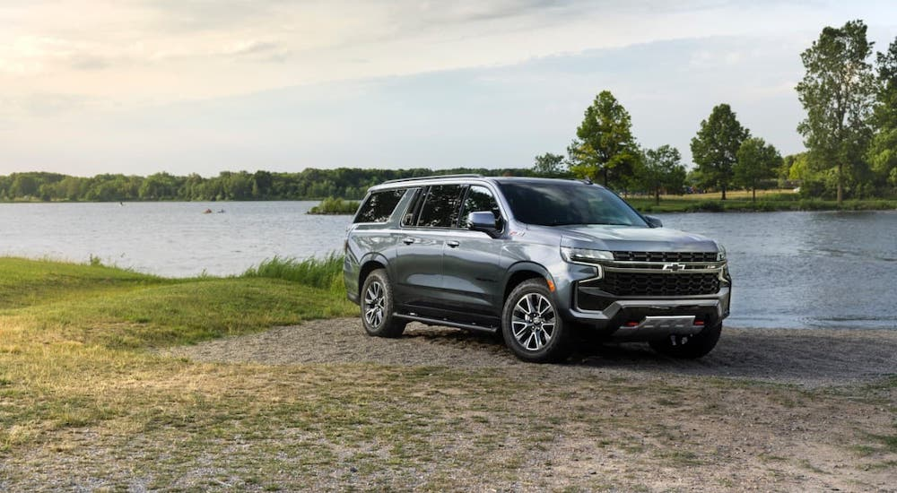 A gray 2021 Chevy Suburban Z71 is parked in front of a lake.