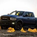 A blue 2021 Ram 2500 Power Wagon is in front of a sunset.