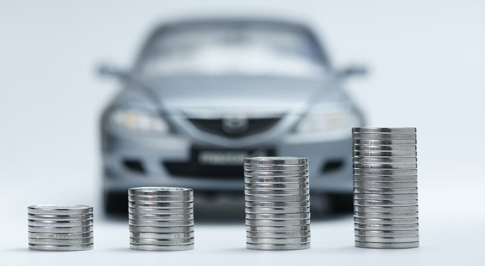 A close up shows increasing stacks of quarters with a blurred car in the background.