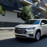 A white 2019 Chevy Traverse is driving on a city street after leaving a used Chevy dealer.
