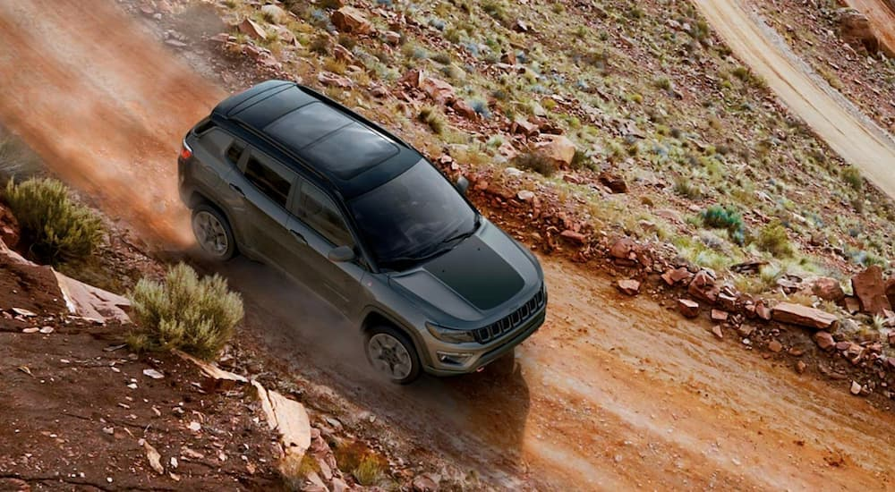 A grey 2019 used Jeep Compass is shown from above on a red dirt road.