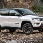 A white 2020 used Jeep Compass is parked on a rocky river bank.