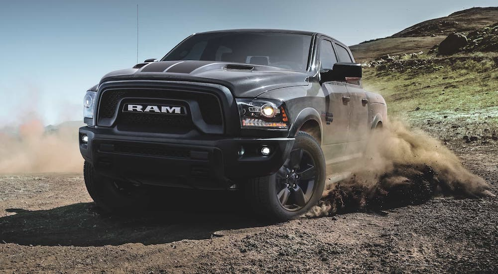 A popular used Ram truck in Lexington, a black 2020 Ram 1500 Classic Warlock, is kicking up dirt on a trail.