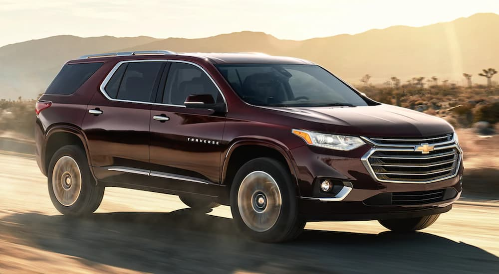 A maroon 2021 Chevy Traverse is speeding down a dusty road.