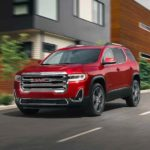 A red 2021 GMC Acadia is shown driving past modern buildings.
