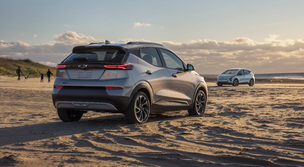 A silver 2022 Chevy Bolt EUV is parked on a beach and shown from a rear angle.