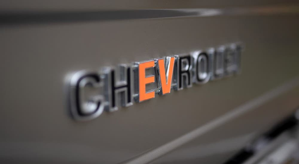 A closeup shows the badging on a gold SEMA 360 Blazer concept where the 'EV' in Chevrolet is orange.