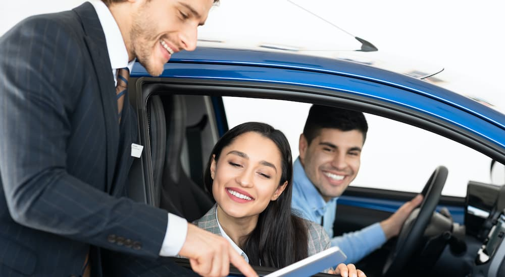 A couple is looking over paperwork with a salesman with sitting in a blue used car.