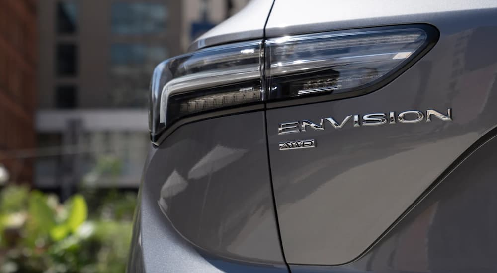 The rear tail light of a 2021 Buick Envision is shown in a city.