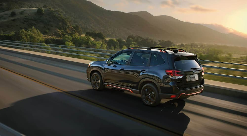 A black 2021 Subaru Forester is shown from the side driving on an open road as the sun sets.