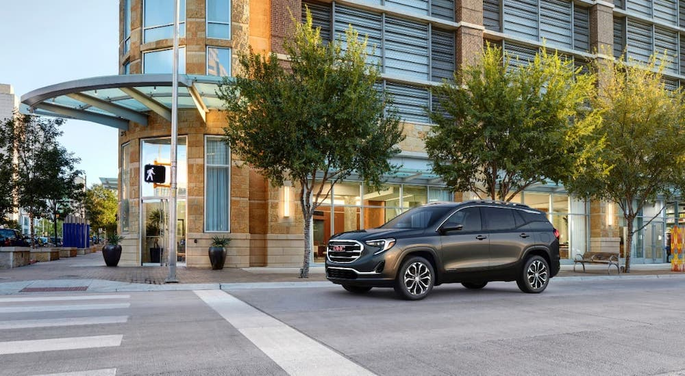 A dark gray 2021 GMC Terrain is parked at a stop sign on a city street.