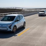 Two silver 2022 Chevy Bolt EVs are driving on an empty highway.
