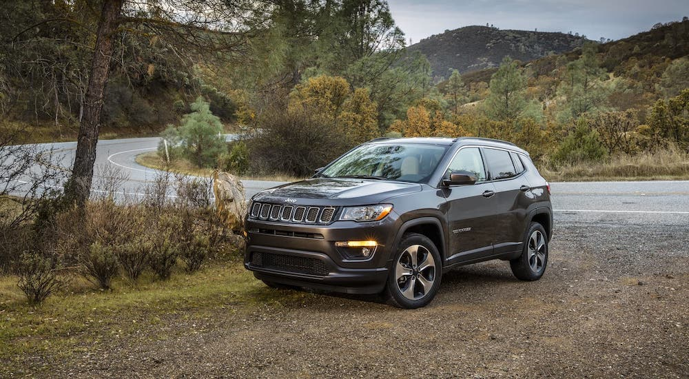 A gray 2020 Used Jeep Compass is parked on a dirt area next to a highway.