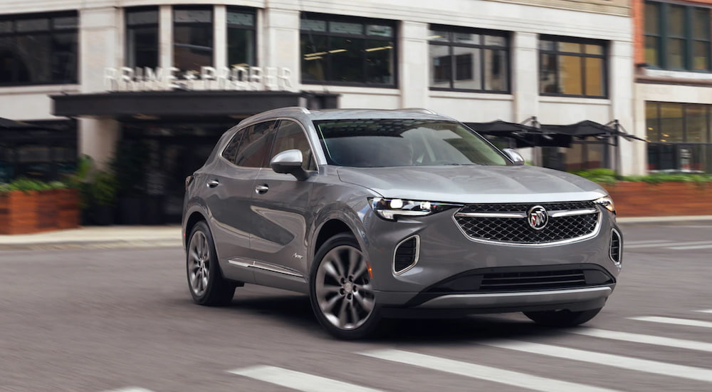 A grey 2021 Buick Envision is driving through an intersection.