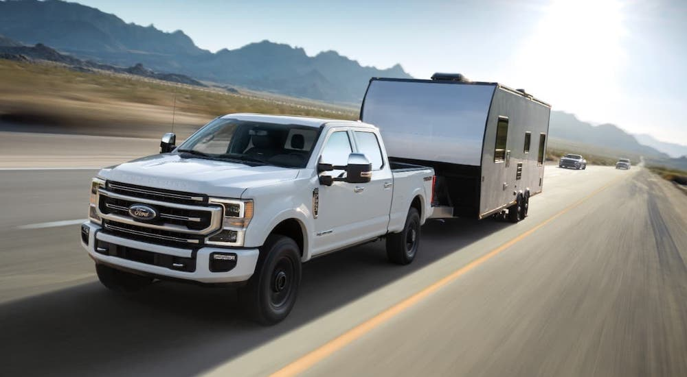 A white 2021 Ford F-250 is towing a camper on a highway.