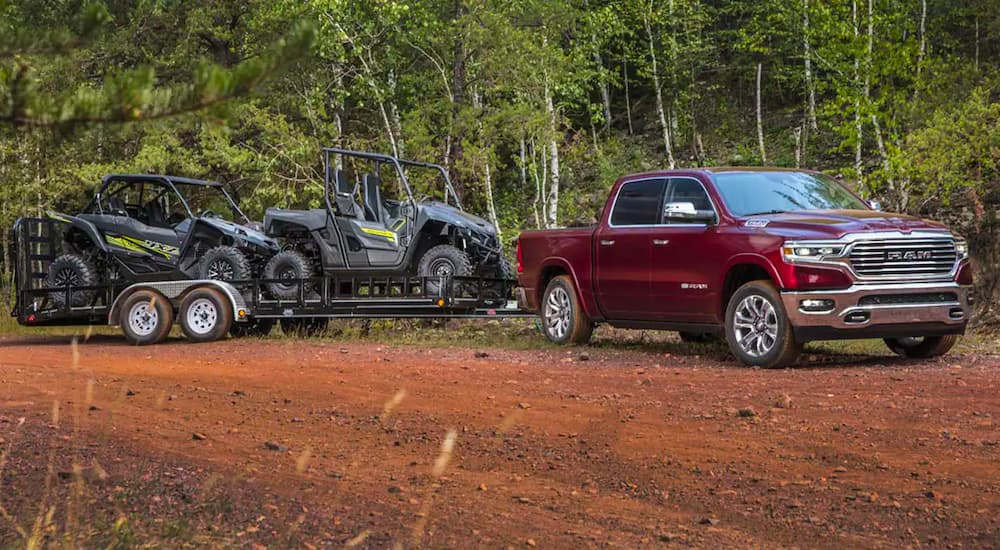 A red 2021 Ram 1500 is parked on dirt with a trailer filled with two UTVs.