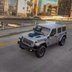 A silver 2021 Jeep Wrangler 4xe is shown from a high angle driving on a city street.