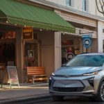 A silver 2022 Chevy Bolt EUV is parked in front of an outdoor gear store.